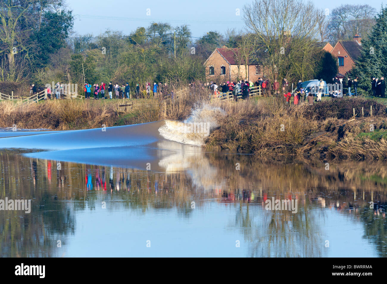 People watching the Severn Bore breaking against the riverbank at Minsterworth, Gloucestershire on 1/3/2010 - Stock Image