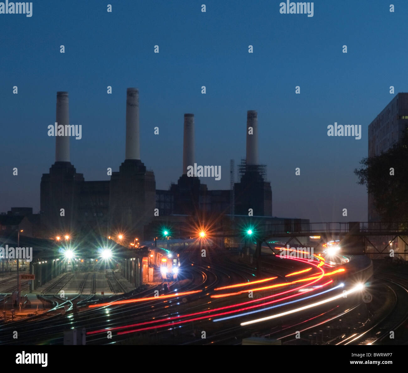Trains entering and leaving Victoria Station in the evening rush hour with Battersea Power Station in the background. - Stock Image