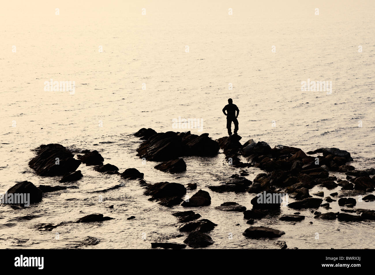 Lone figure standing on rocks looking at sea - Stock Image