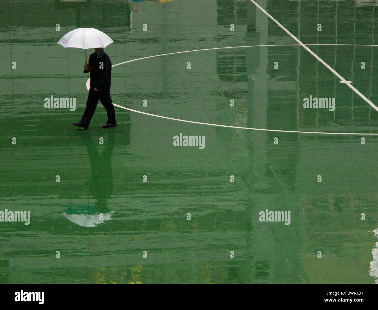 A man with a white umbrella crossing a football pitch in the rain in Hong Kong - Stock Image