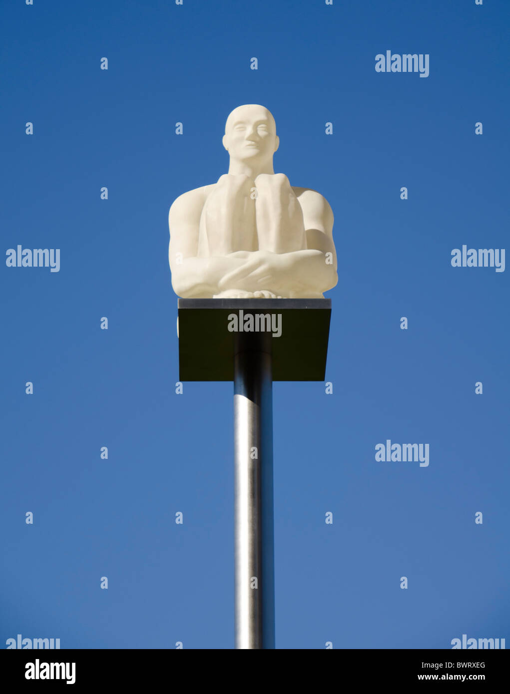 Lonely man sitting on a pole - Stock Image