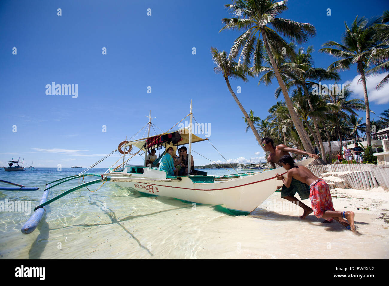 Filipinos shove a bangka boat loaded with tourists off of Bulabog Beach in Boracay, Philippines. - Stock Image