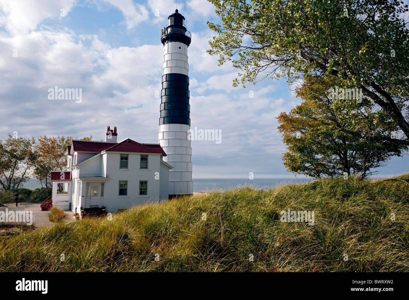 Beautiful clouds float by Michigan's Big Sable Lighthouse (1867) and Lake Michigan in Ludington State Park. - Stock Image
