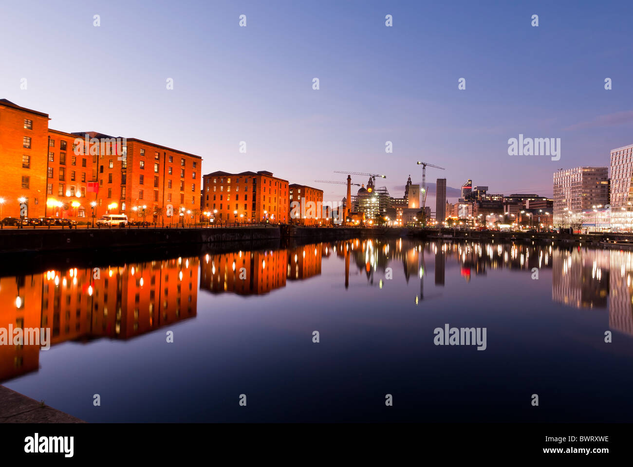 Warehouses reflected in water at the Albert Docks, Liverpool, England, UK - Stock Image