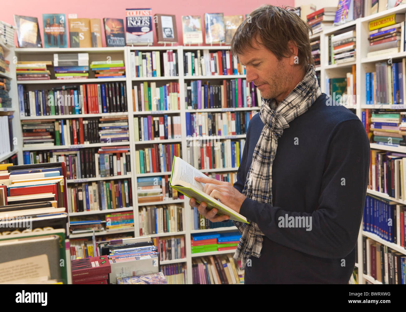 Forty year old man reading in second hand book shop. - Stock Image