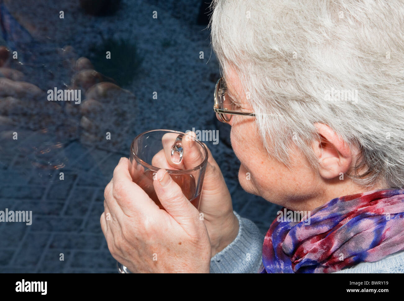 Pensive senior woman holding a warm drink looking out through a window on a cold dark night with snow outside in - Stock Image