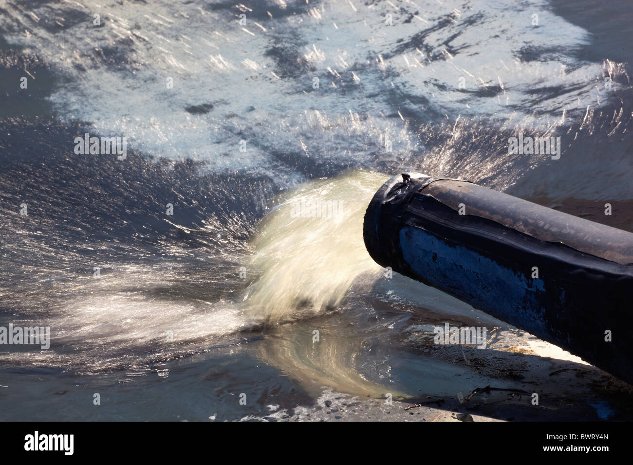 Water gushing from pipe into reservoir. - Stock Image