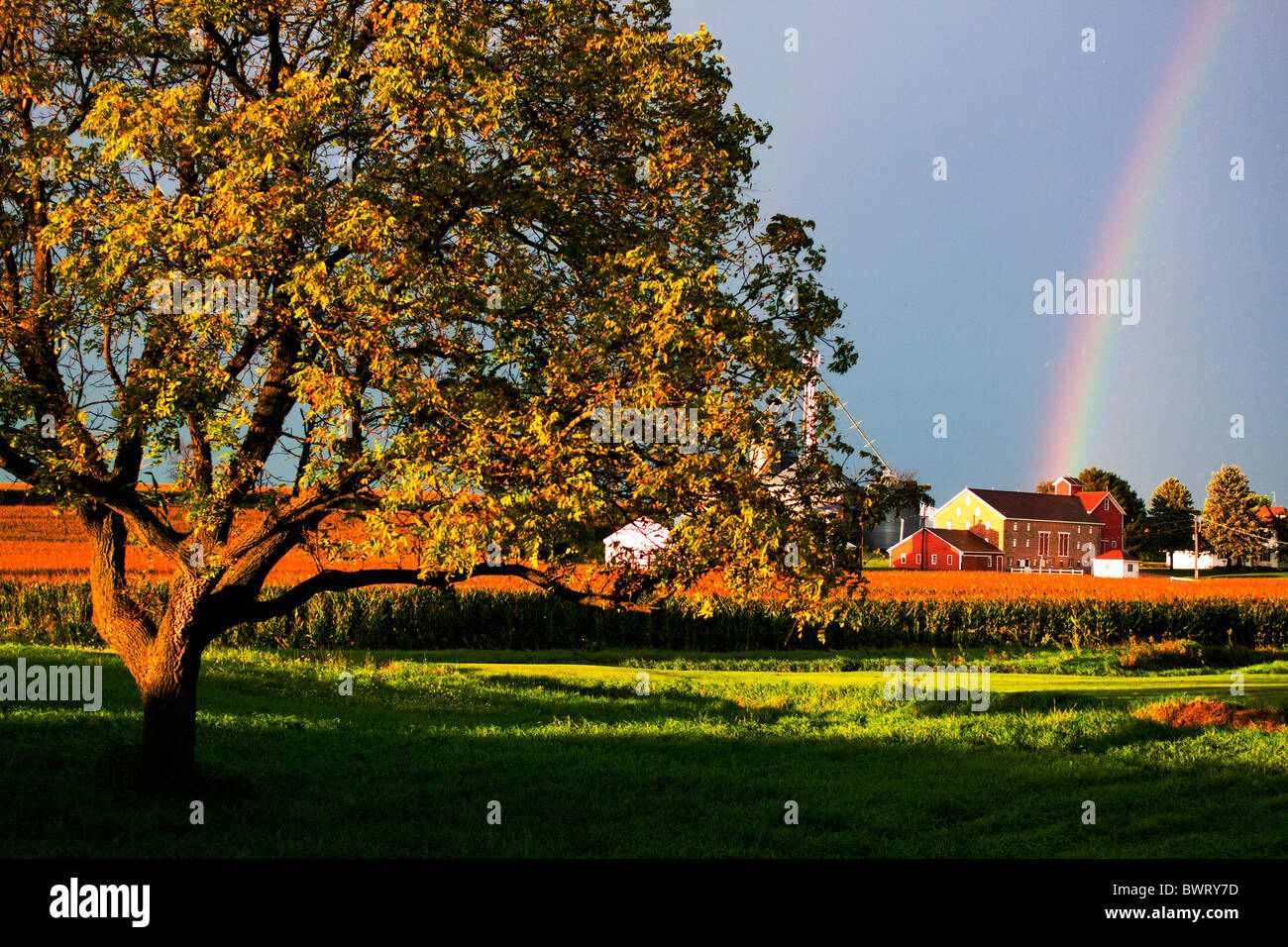 A double rainbow has formed over a farm on the prairie of Illinois. - Stock Image