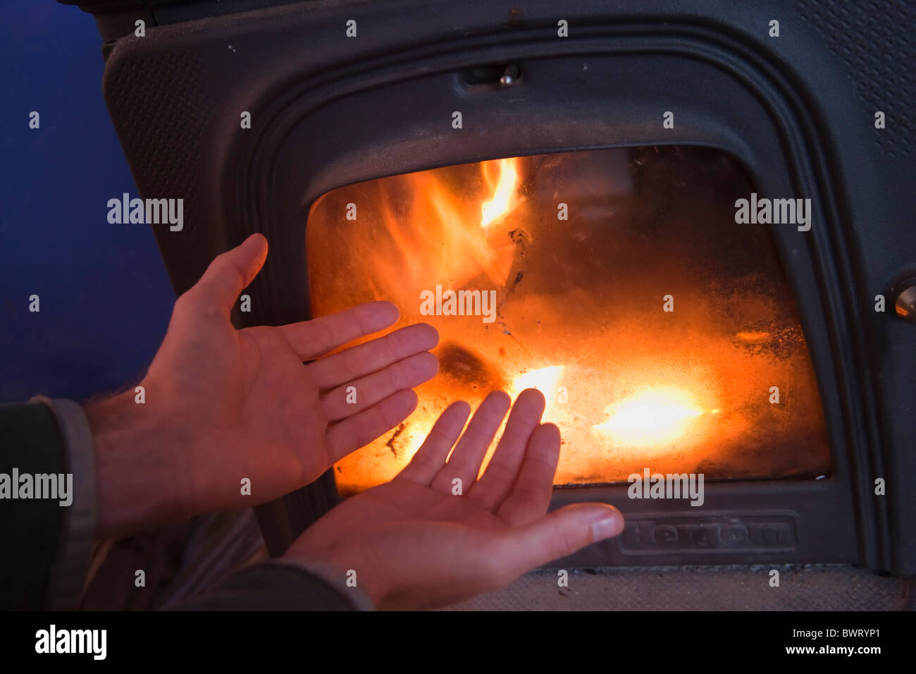 Hands being warmed in front of wood burning stove - Stock Image