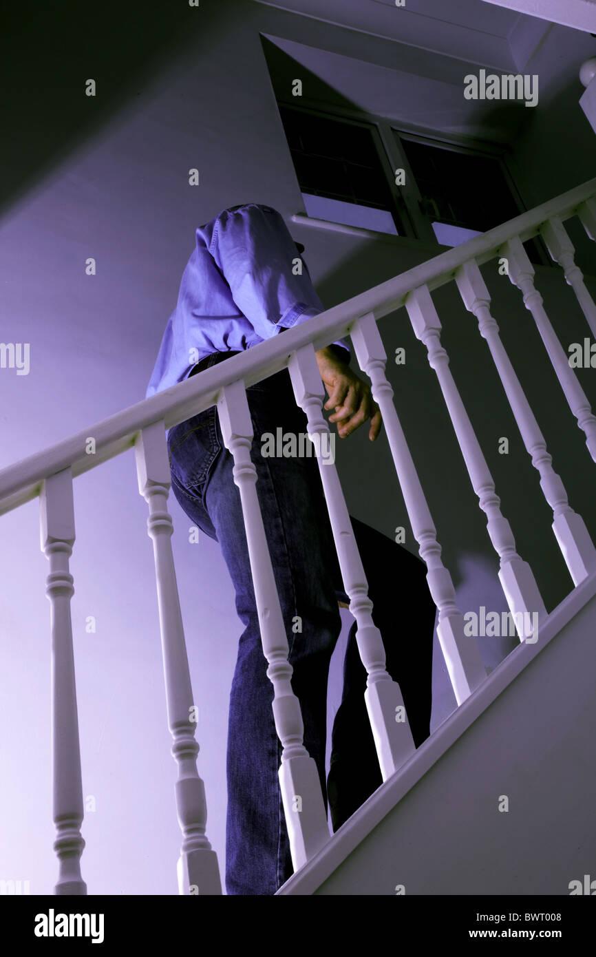 Man walking up a dark stairway - Stock Image