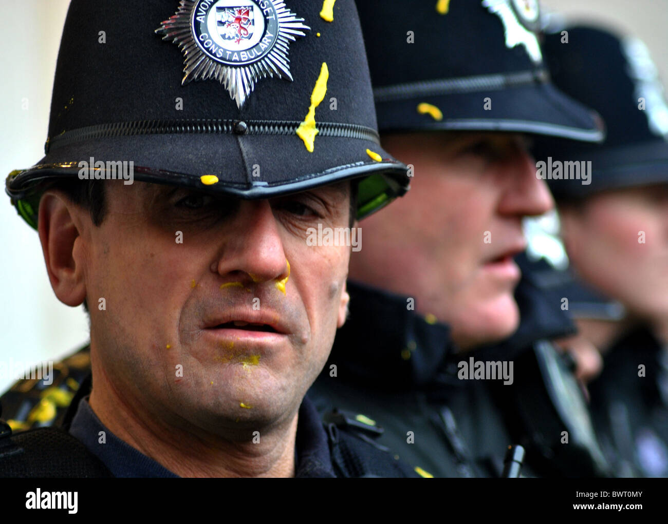 Police officers are covered in mustard, thrown at them by students protesting against rising tuition fees at Bristol - Stock Image