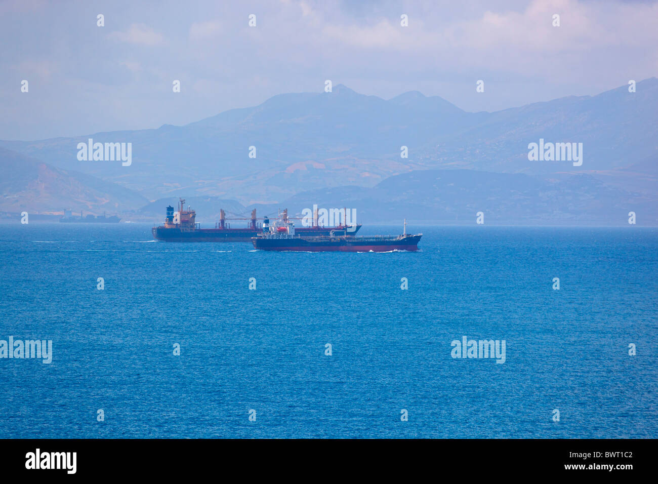 Cargo ships passing through the Straits of Gibraltar between Spain and Morocco. Morocco is seen in the background. - Stock Image