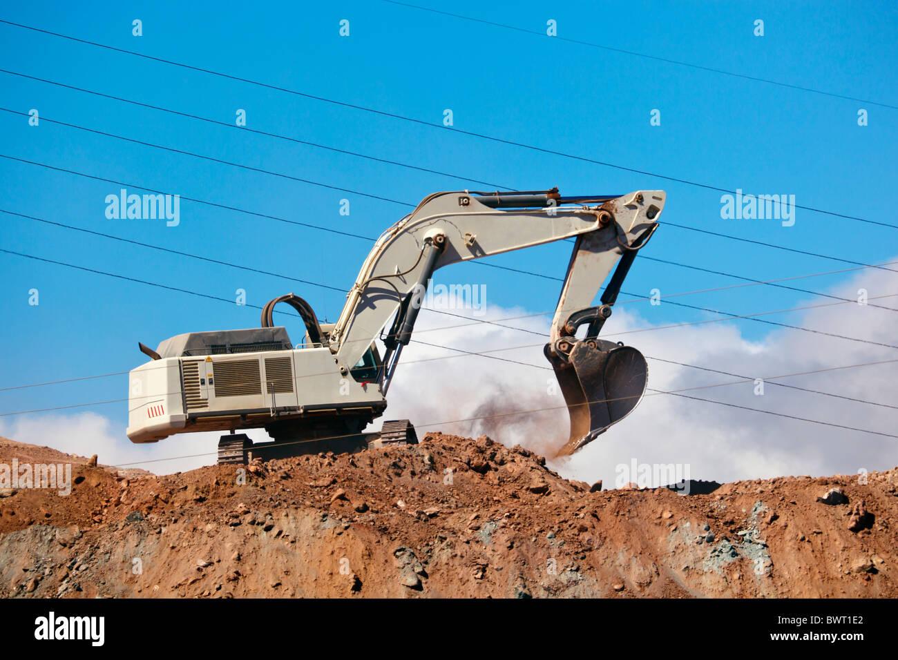 Mechanical backhoe shovel at work on a building site near Algeciras, Cadiz Province, Spain. - Stock Image