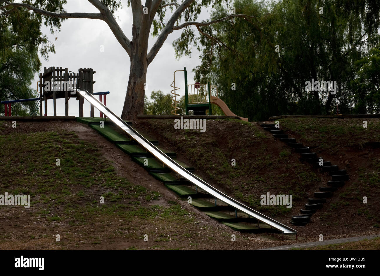An Australian playground with a slippery dip or slide and a staircase made of re-purposed car tires. - Stock Image