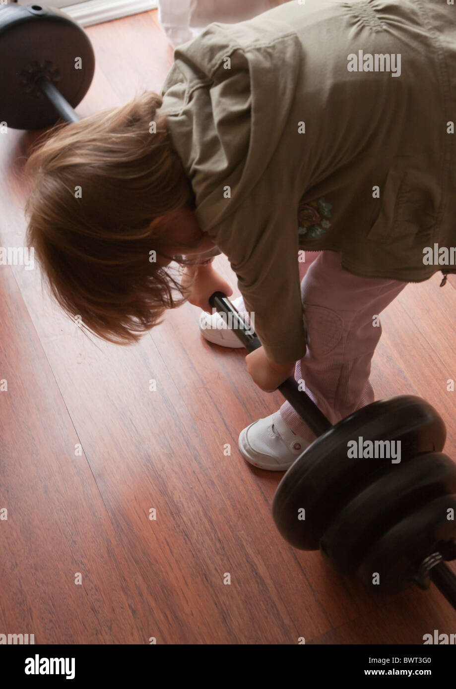 Three year old girl trying to lift heavy weights. - Stock Image