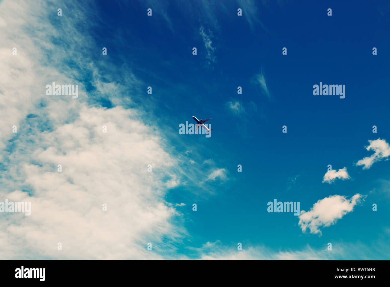 Commercial airliner in cloudy sky - Stock Image