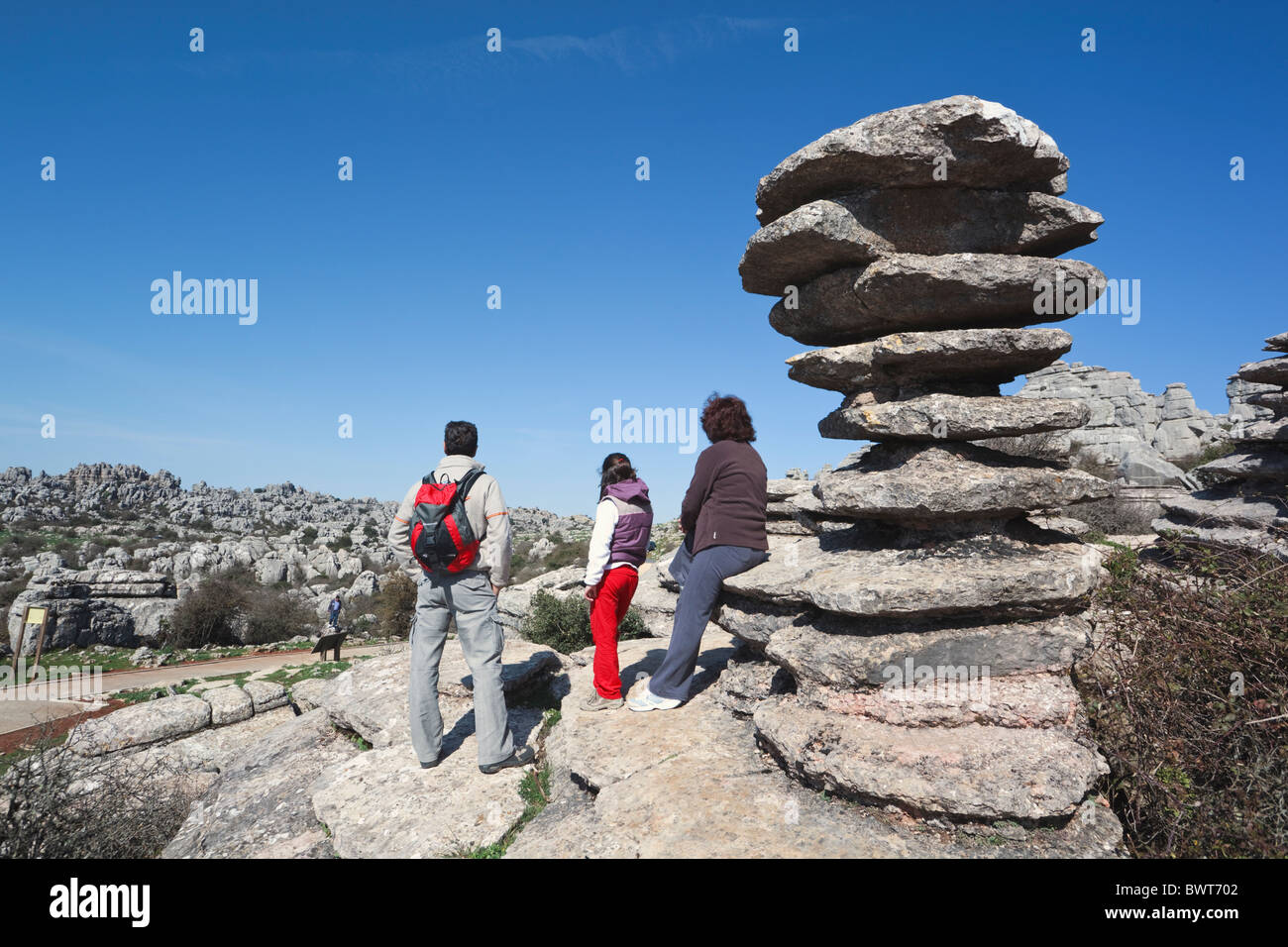 Family at rock formation known as El Tornillo, or the Screw in El Torcal Park Nature Reserve near Antequera, Spain. - Stock Image