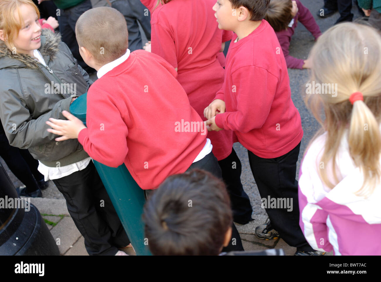 UK English Primary school children playing and talking outside. - Stock Image