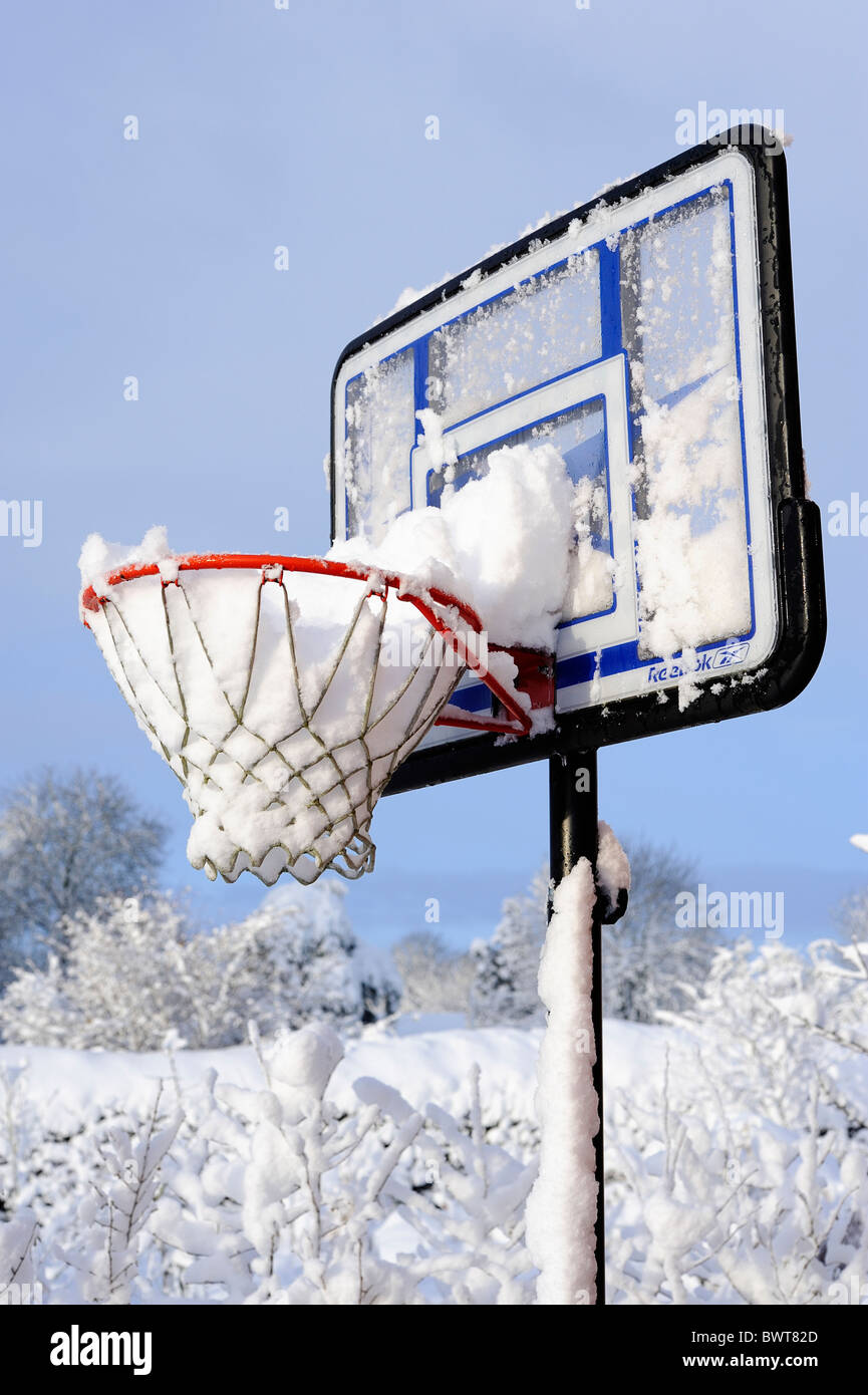 Heavy fall of snow fills an outside basketball hoop - Stock Image