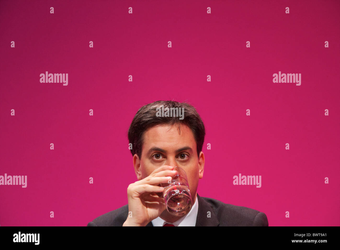 Ed Miliband takes a sip of water while listening to a speech during the Labour Party Conference in Manchester on - Stock Image