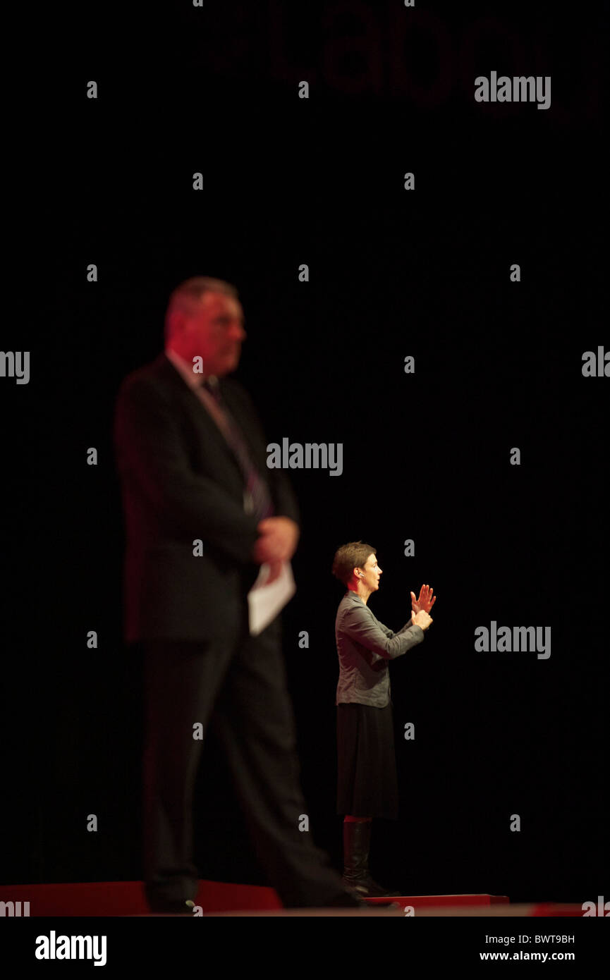 A sign language interpreter commnicates to the audience while a party official dominates the foreground during the - Stock Image