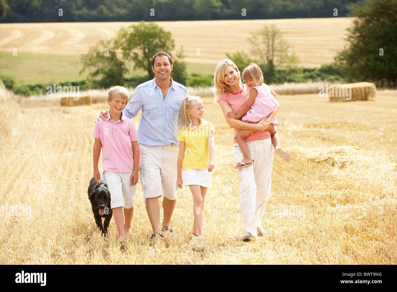 Family Walking Together Through Summer Harvested Field - Stock Image