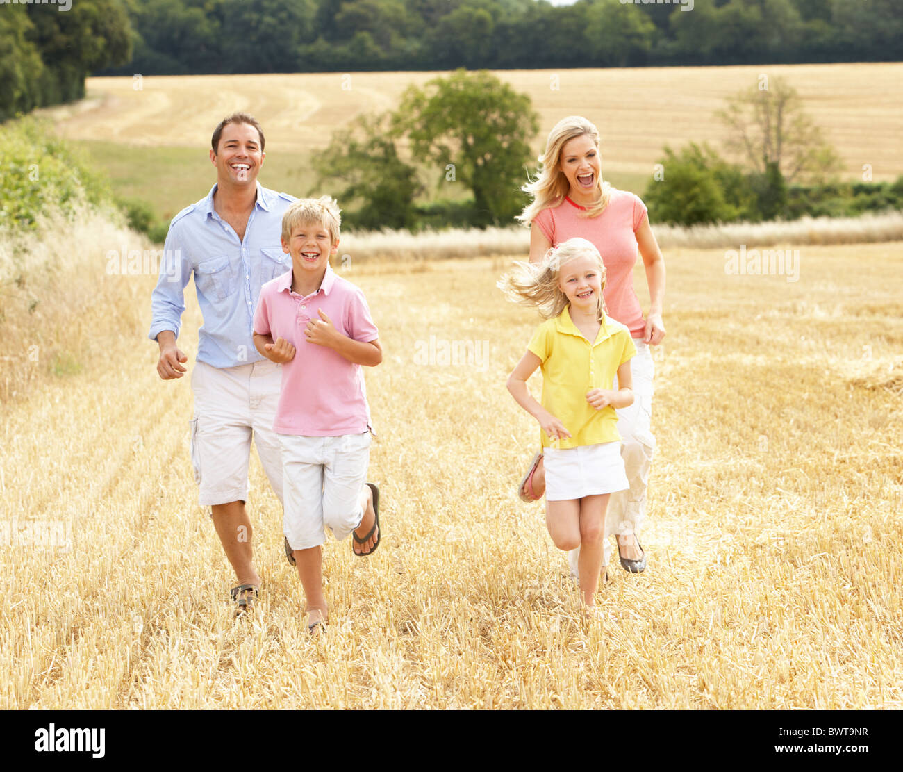 Family Running Together Through Summer Harvested Field - Stock Image