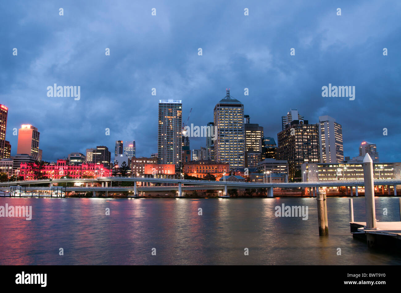 Looking at the Brisbane skyline at dusk across the Brisbane River from Southbank. - Stock Image
