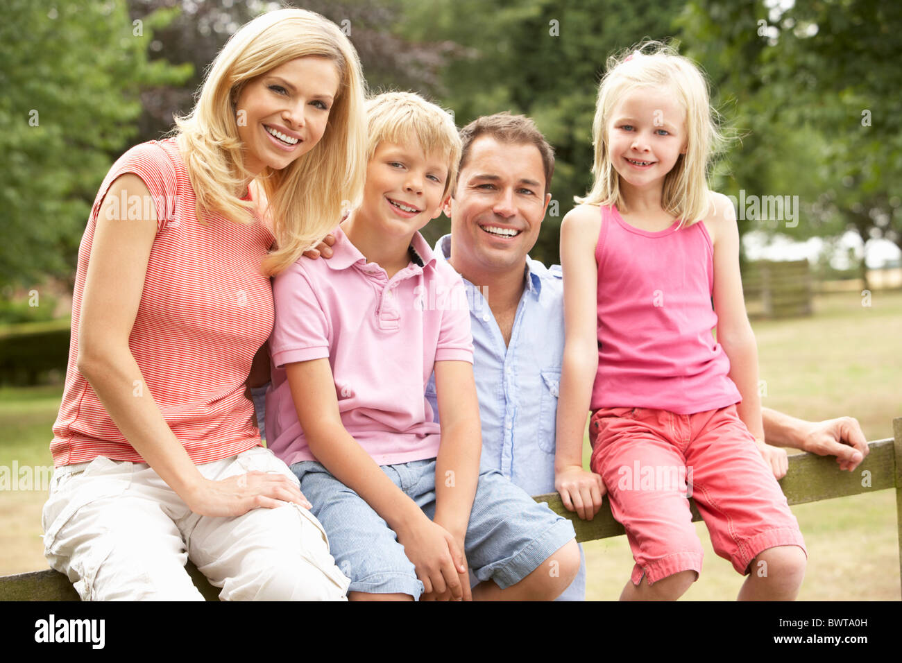 Portrait Of Family Sitting On Fence In Countryside - Stock Image