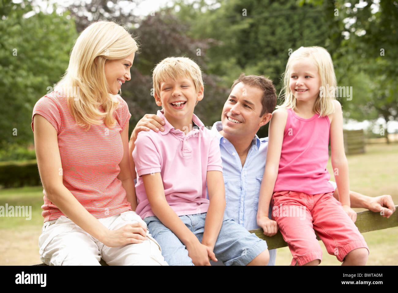 Portrait Of Family Sitting On Fence In Countryside Stock Photo