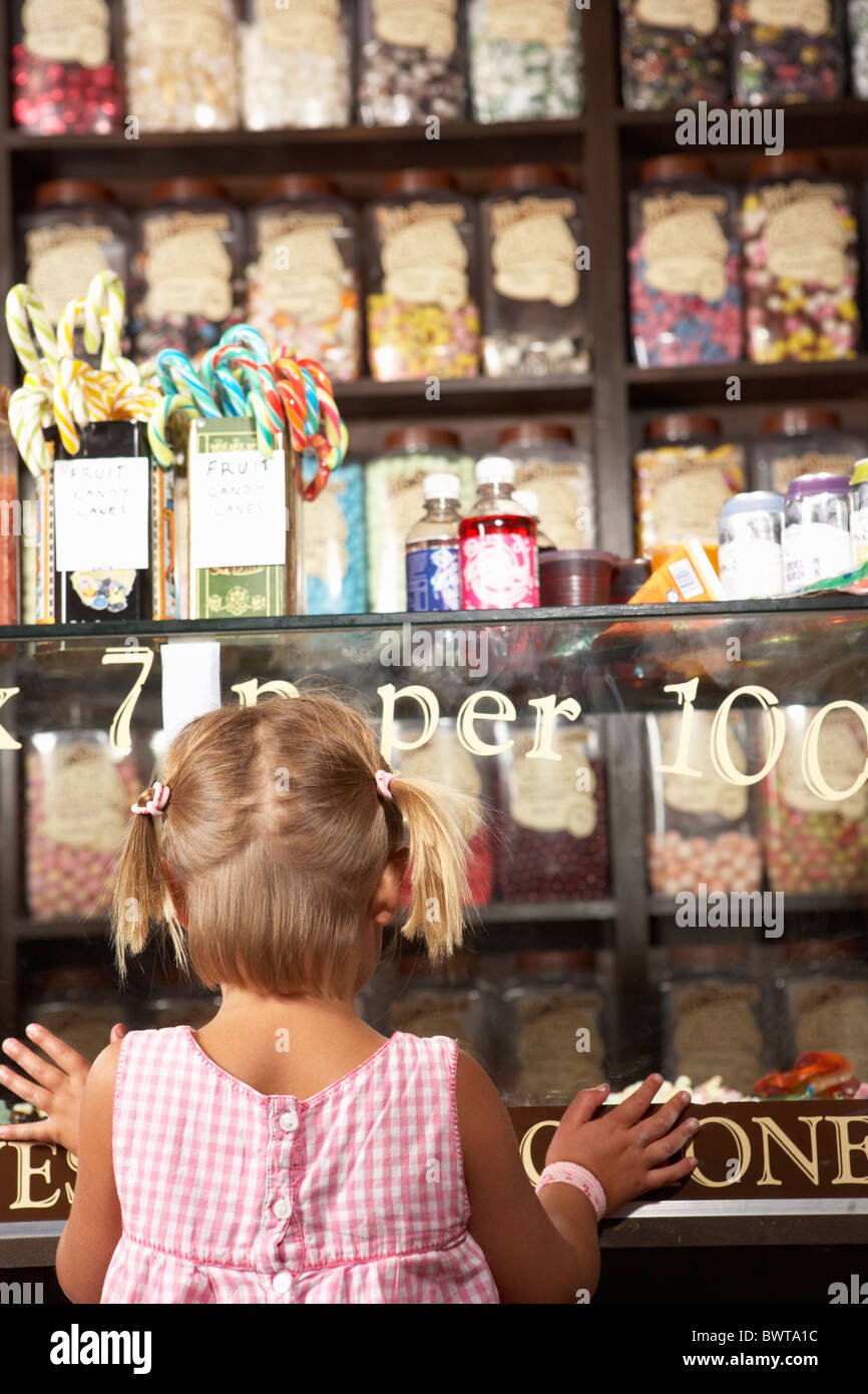 Excited Girl Standing In Sweet Shop Stock Photo