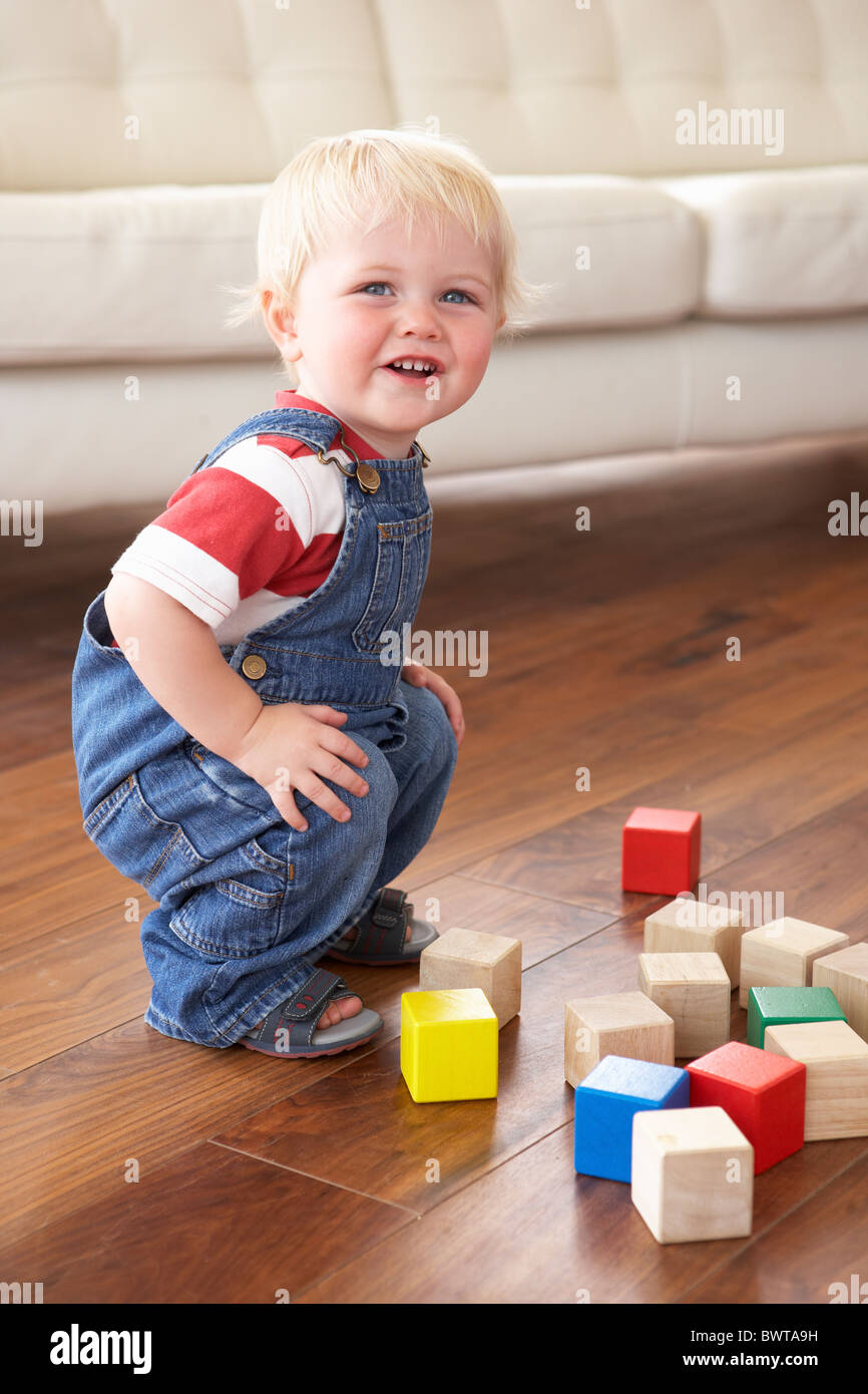 Young Boy Playing With Coloured Blocks At Home - Stock Image
