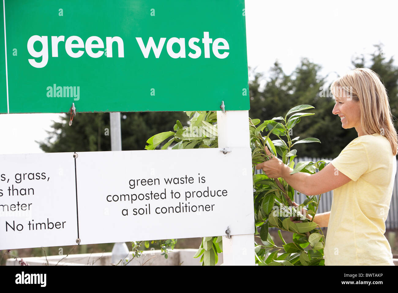 Man At Recycling Centre Disposing Of Garden Waste - Stock Image