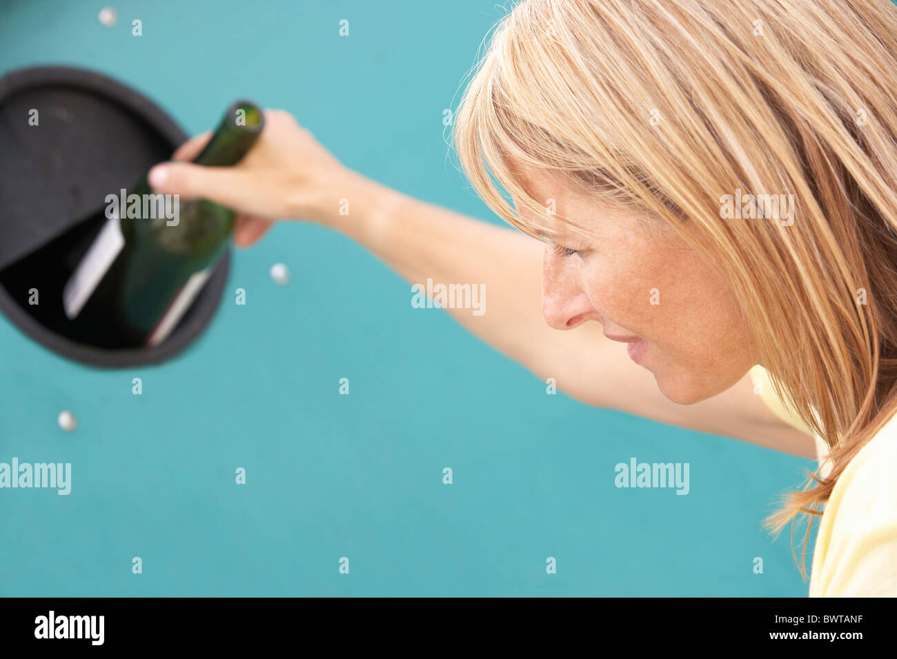 Woman At Recycling Centre Disposing Of Glass At Bottle Bank - Stock Image