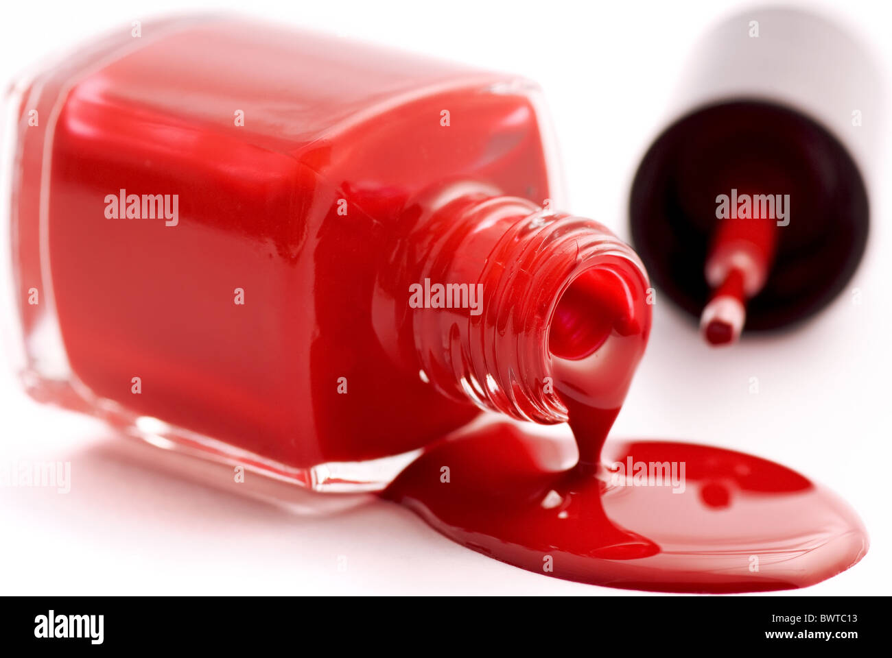Open Flask with dropping nail polish as closeup on white background - Stock Image