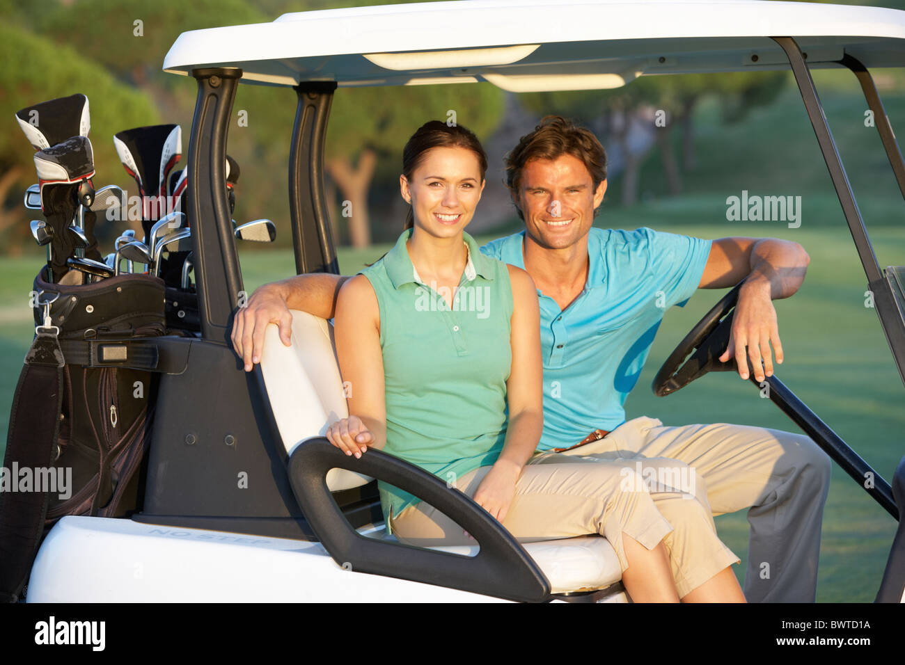 Couple Riding In Golf Buggy On Golf Course - Stock Image