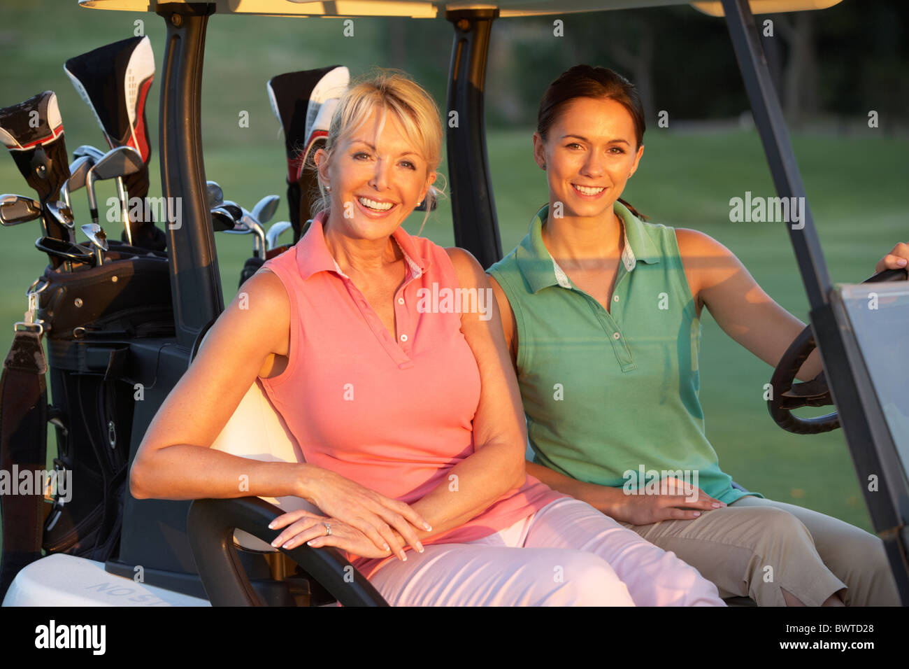 Two Female Golfers Riding Golf Buggy Golf Course - Stock Image