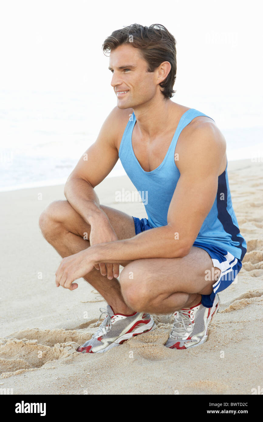 Man Fitness Clothing Resting After Exercise Beach - Stock Image
