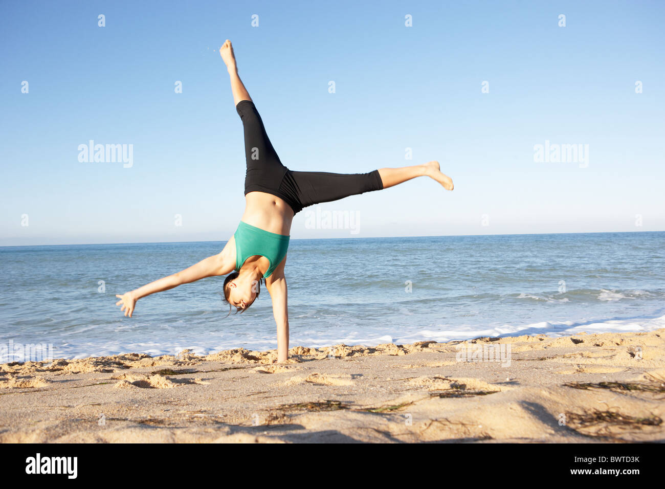Young Woman Fitness Clothing Cartwheel Beach - Stock Image