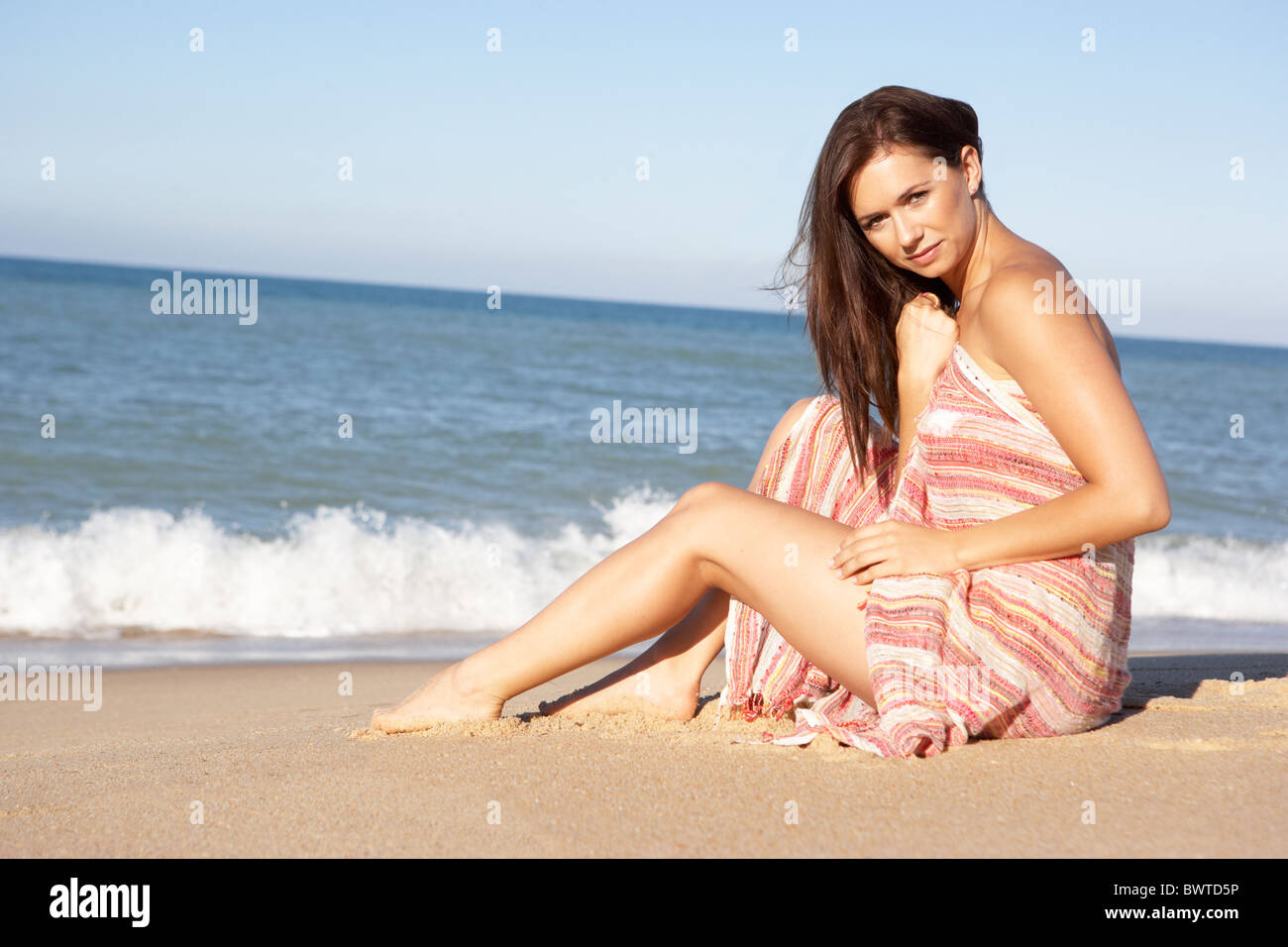 Young Woman Relaxing On Beach Wearing Wrap - Stock Image