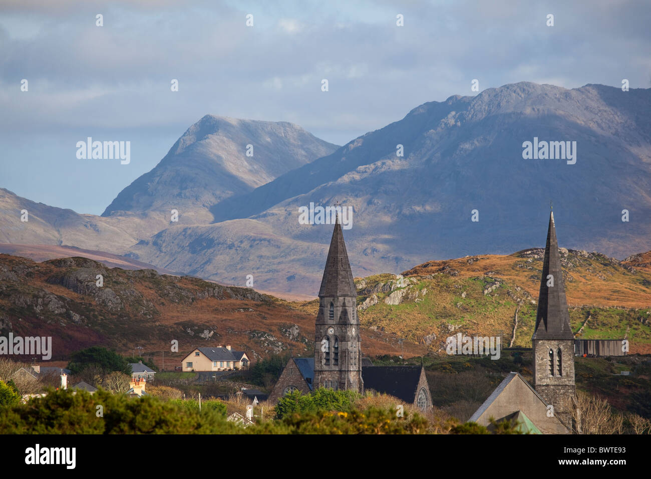 Church spires of the Connemara town of Clifden, in Ireland, with the Twelve Bens mountains in the background - Stock Image