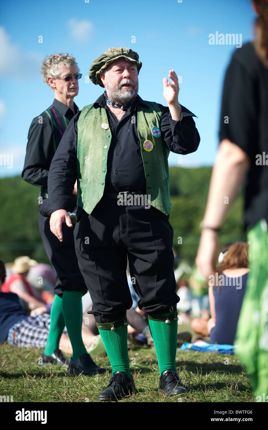 A man announces that an traditional folk dance performance is about to begin on the final day of Bestival 2010 in - Stock Image