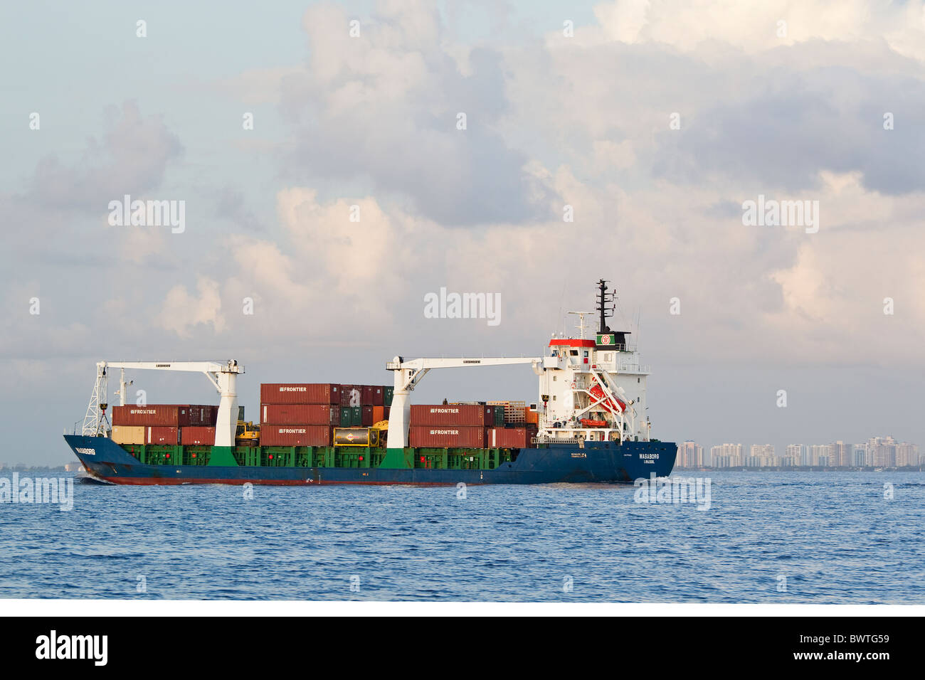 Cargo ship at sea near city, Daytona, Florida, with shipping containers - Stock Image