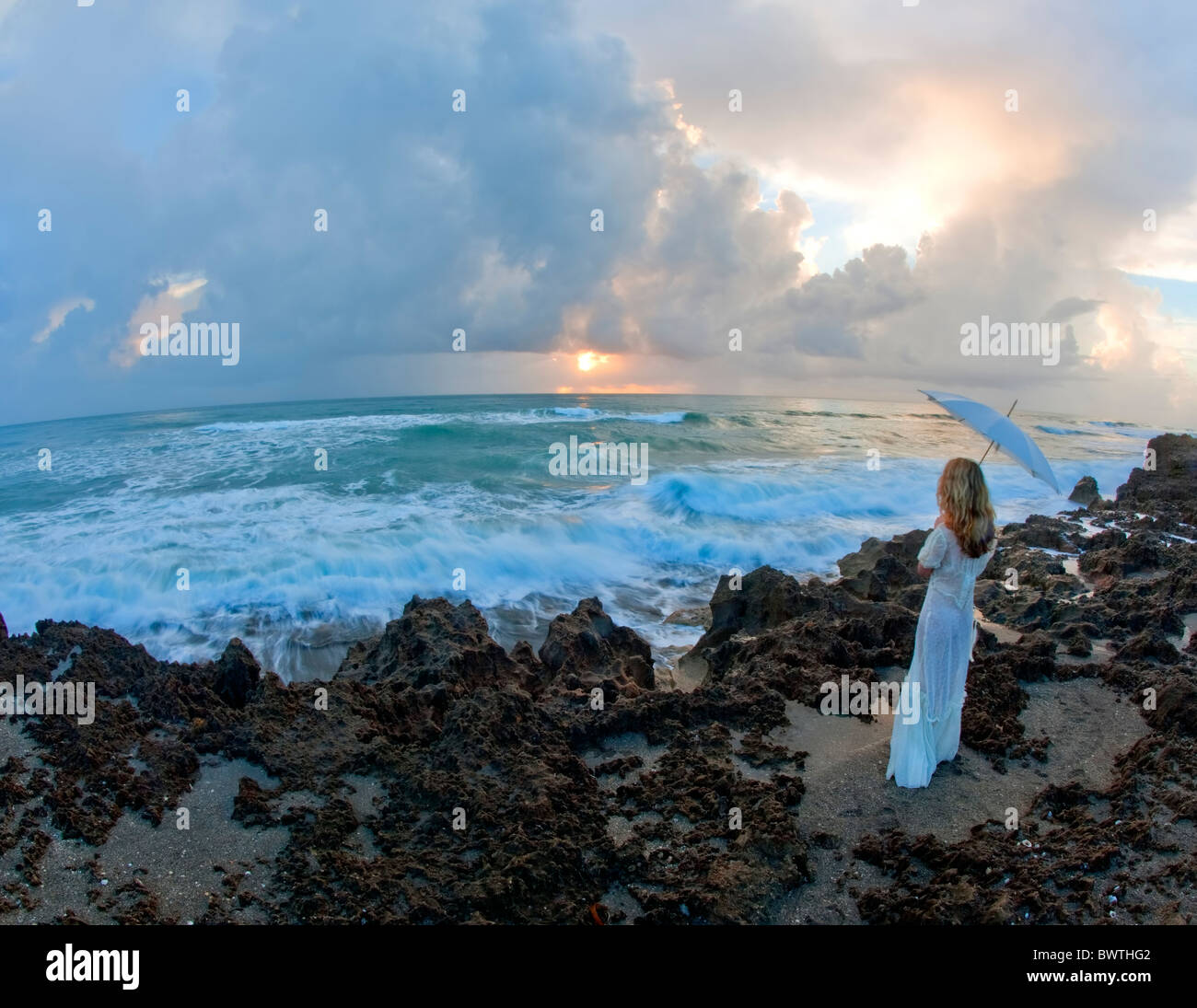 Young woman holding umbrella standing on rocks near ocean - Stock Image