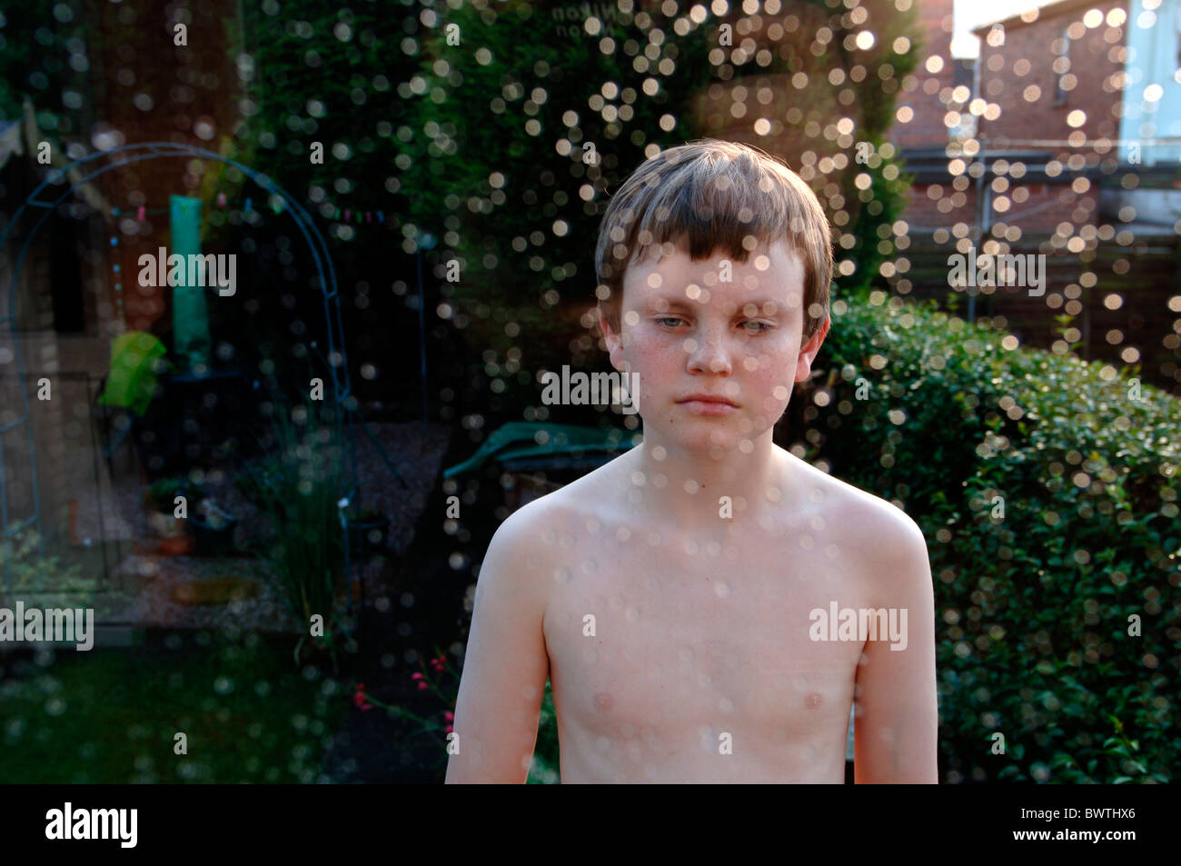 A 14yr Old Boy Standing In Front Of Rain Speckled Glass. - Stock Image