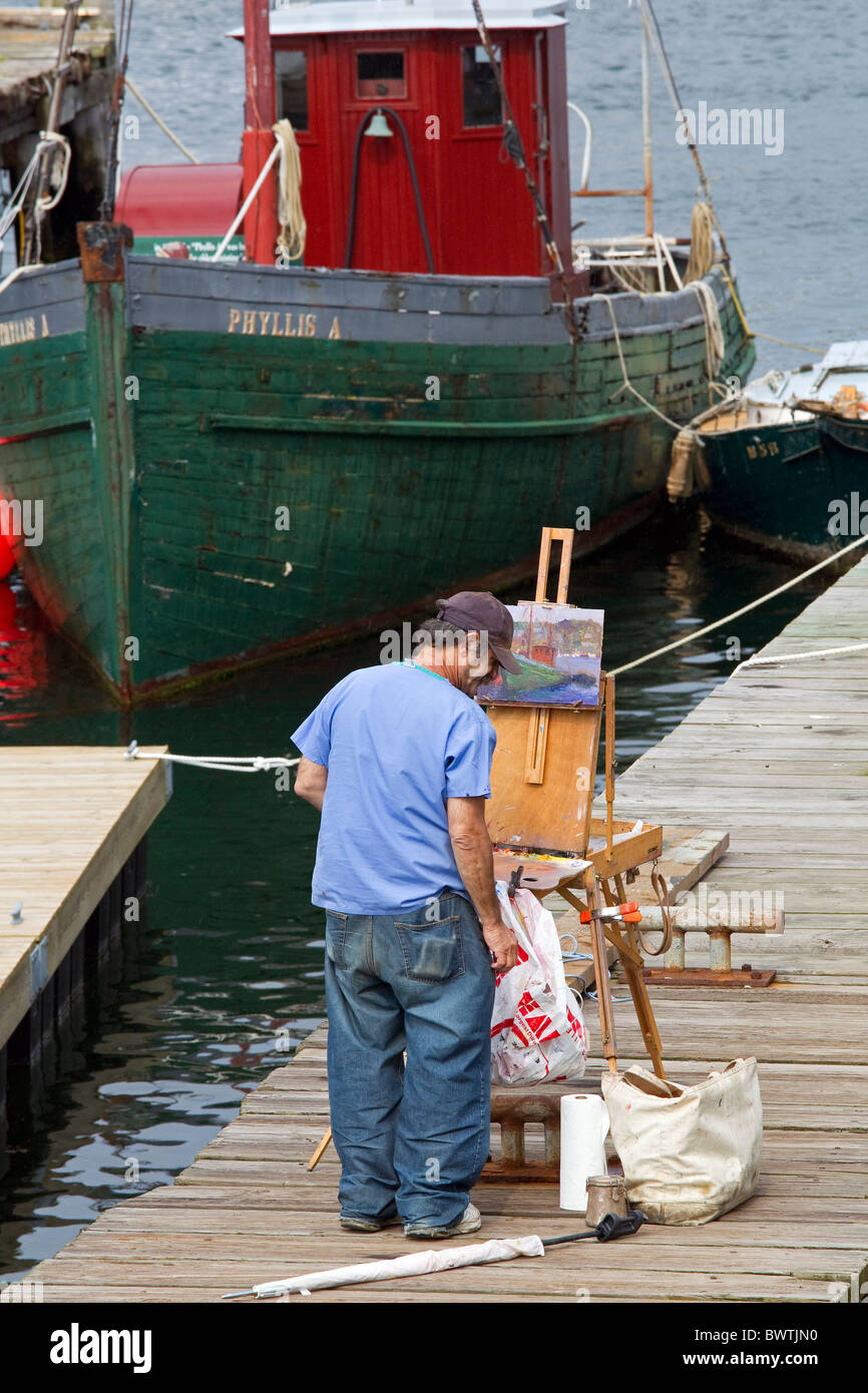 Artist paints tugboat at dock in Rocky Neck artists colony, Gloucester, Massachusetts, USA - Stock Image