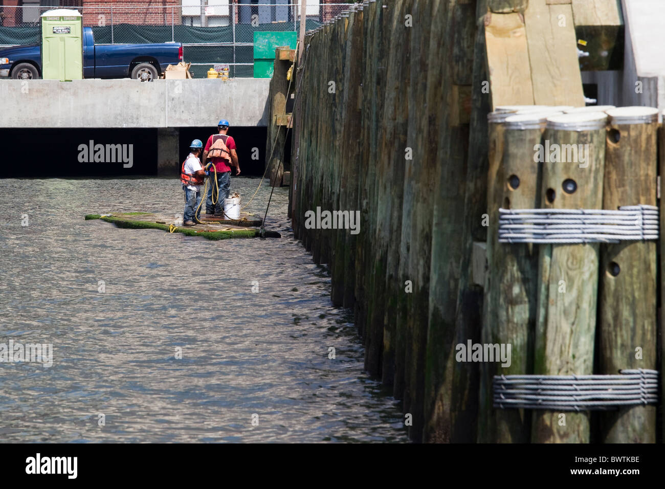 Two dock workers on raft beside dock in New York City, USA - Stock Image