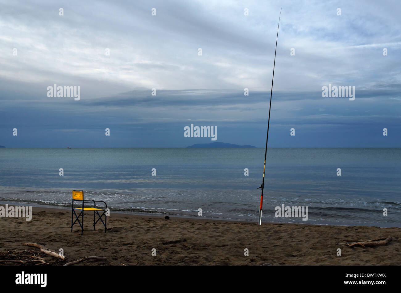 Yellow chair and fishing rod on the beach of Parco Naturale della Maremma, Symbolic picture,Tuscany, Italy - Stock Image