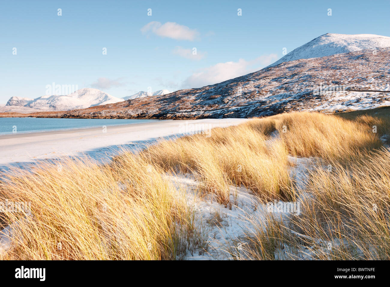 Maram grass and a layer of snow on the dunes at traigh Rosamol on the isle of Harris with Ben Dubdh and the Harris - Stock Image