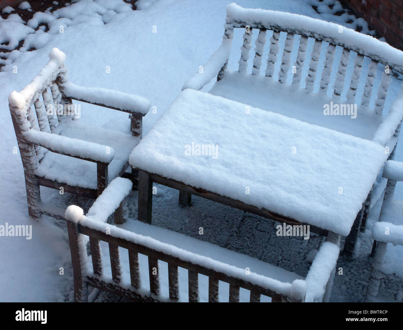 Snow Covering Outdoor Table And Chairs On Patio During Winter, London,  England.